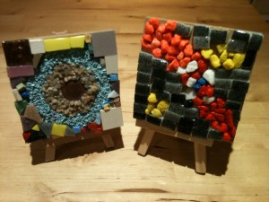 Mini easels displaying mosaics made from small stones, beads and a coin.  (These items may be found at home, not included in the Craft Kit or Craft Activity Bag)